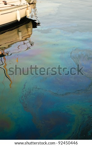 Rainbow oil pollution in the water leaked from the nearby boat.