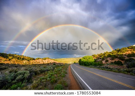Rainbow over road landscape. Road rainbow landscape. Rainbow road view