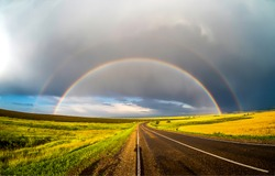 Rainbow over rural road landscape. Rainbow road view. Rainbow road landscape