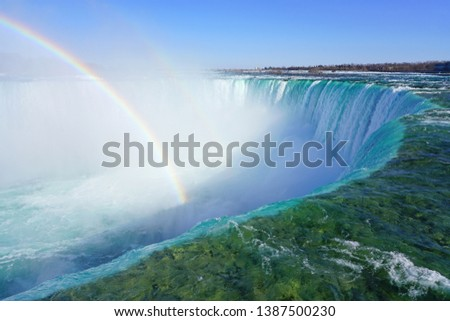 Rainbow over the Horseshoe Falls over frozen ice and snow on the Niagara River in Niagara Falls in March 2019 #1387500230