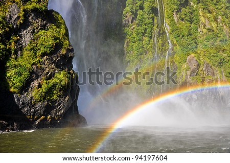 Rainbow over the Milford Sound waterfall. New Zealand