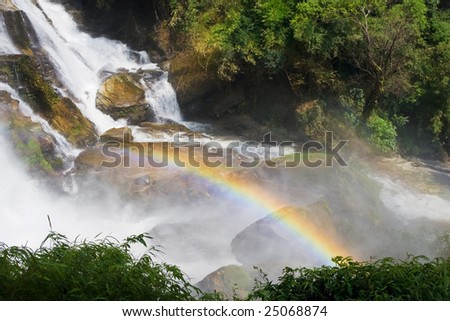 Rainbow over the waterfall in tropical forest.