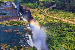 Rainbow over Victoria Falls in Zimbabwe, sunny day in Africa