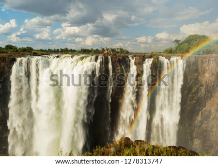 Rainbow over Victoria Falls on Zambezi River. Victoria falls is a waterfall in southern Africa on the Zambezi River at the border of Zambia and Zimbabwe. #1278313747