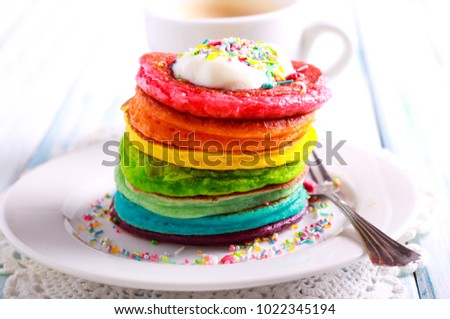 Rainbow pancakes, served in pile on plate #1022345194