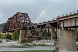 Rainbow passing behind large steel girder train bridge in small midwestern town