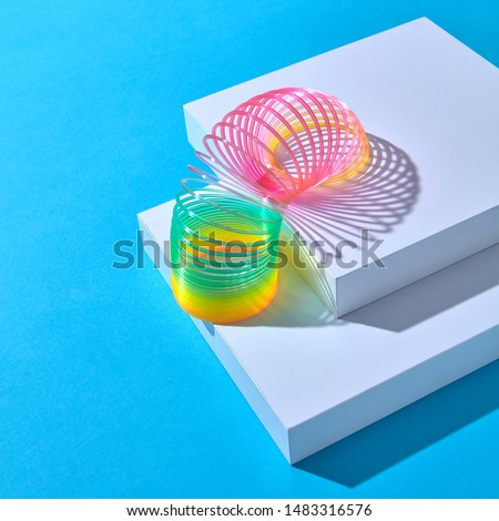 Rainbow plastic multicolored spring spiral goes down white stairs step by step on a pastel background with shadows, copy space.