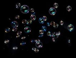 Rainbow soap bubbles on black background.