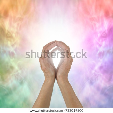 Rainbow Spectrum Energy healing hands - female  hands with fingertips touching on a wispy ethereal rainbow colored background and a ball of white light plus copy space all around