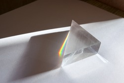 Rainbow spectrum of colors caused by breaking and dispersion of sunlight in a glass prism. Physics experiment.
