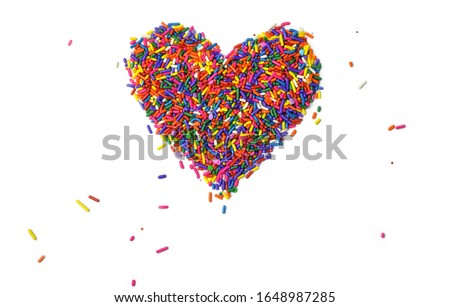 Rainbow sprinkles in the shape of a heart over white background