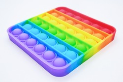 Rainbow Square Fidget Toys Pop-it on the light background. Push Pop Bubble. Popular Relaxing square shape silicone stress relief toy. View from an angle in perspective.