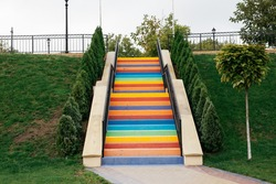 Rainbow stairs. Stairs painted in different colors surrounded by greenery in a park.