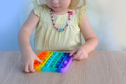rainbow Toy antistress Pop it, small child, a girl of 2 years old presses with her fingers poppit bubbles, plays with anti-stress device for psychological relief