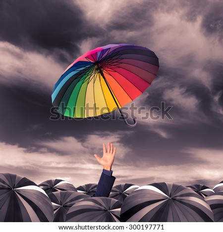 rainbow umbrella fly out from the business man hand amoung the mass of black umbrellas