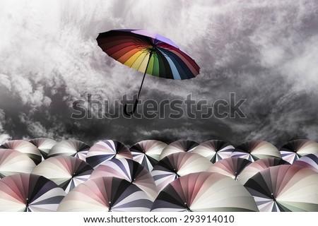 rainbow umbrella fly out the mass of umbrellas