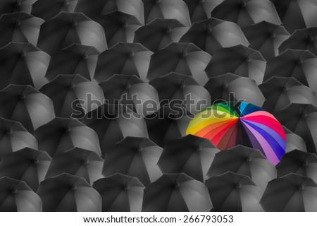 rainbow umbrella in mass of black umbrellas, different concept