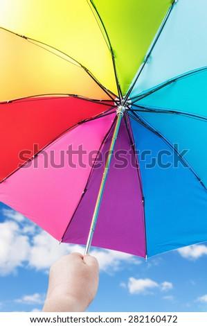 Rainbow umbrella in woman hands against cloudy sky. Focus on the latch closing umbrella