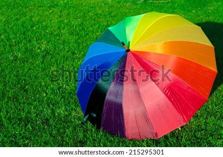 Rainbow umbrella on the green grass in sunny day