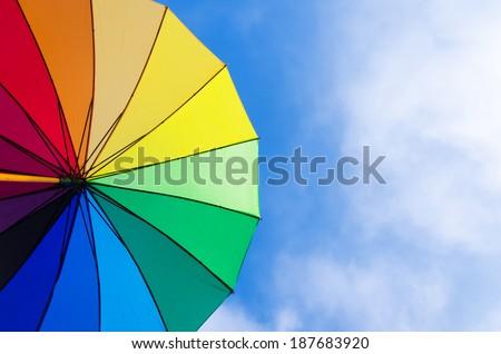 Rainbow umbrella\'s background against a blue sky