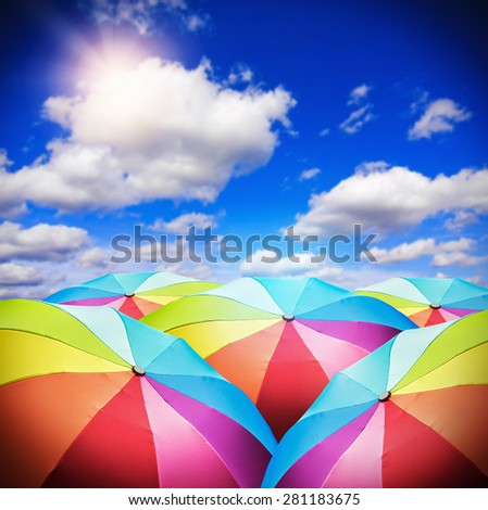 Rainbow umbrellas against the background of the sunny sky. focus on the foreground umbrellas