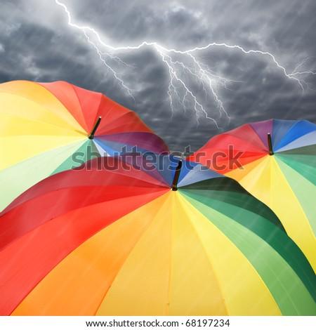 Rainbow umbrellas on dramatic sky background under rain