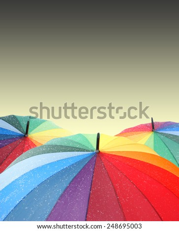 Rainbow umbrellas on sky background