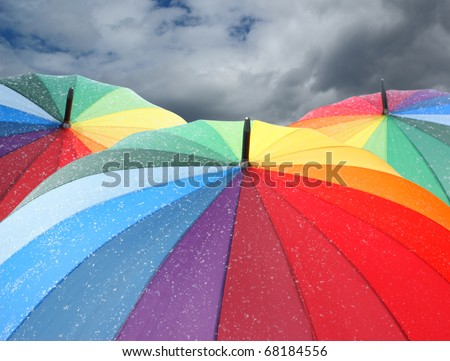 Rainbow umbrellas with snowflakes on dramatic sky background