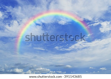 Rainbow with white clouds over blue sky #391143685