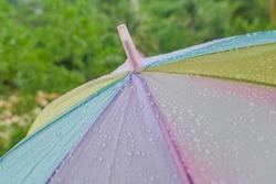 Raindrop or water drops on rainbow umbrella surface. Splash, rain