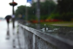 Raindrops fall on the parapet on the city sidewalk. Man with an umbrella in blur. Autumn weather