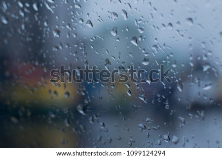 Raindrops falling on glass, abstract blurs - monsoon stock image of Kolkata (formerly Calcutta) city , West Bengal, India #1099124294