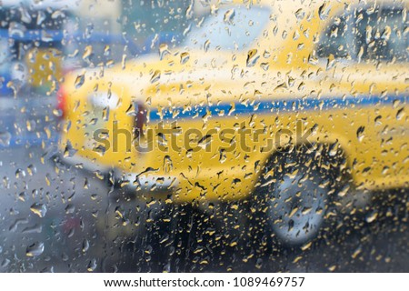Raindrops falling on glass, abstract blurs - monsoon stock image of traditional yellow taxi of Kolkata (formerly Calcutta) city , West Bengal, India #1089469757
