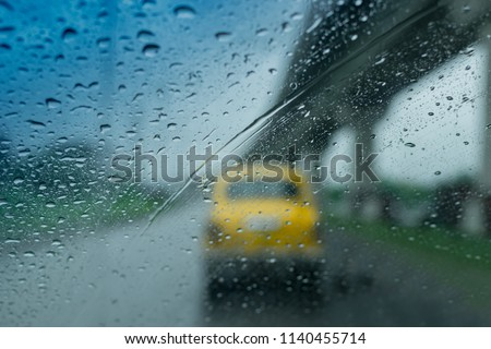 Raindrops falling on glass, abstract blurs - monsoon stock image of traditional yellow taxi of Kolkata (formerly Calcutta) city , West Bengal, India #1140455714