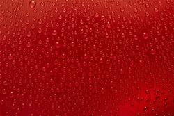 Raindrops on a glass background, red raspberries. Texture of a drop of water on glass.