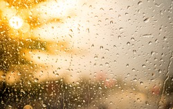 raindrops on a glass window with the sun and warmth tone in background