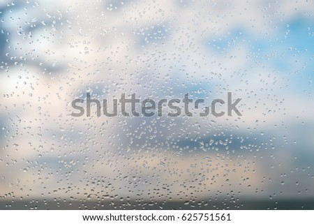 Raindrops on a window glass against blue sky with clouds. #625751561