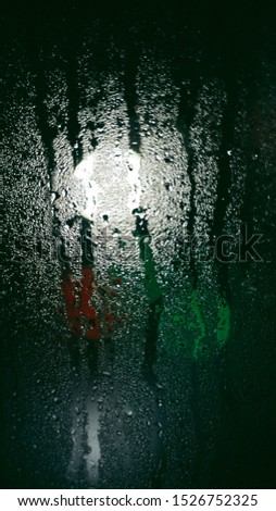 Raindrops on a window pane at night against a background of blurry lights