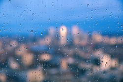 Raindrops on a window pane of glass with blurred background of River Thames and City of London Canary Wharf financial district