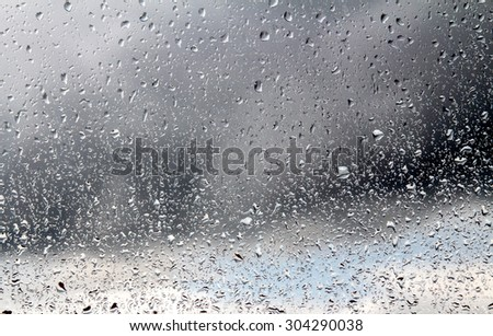 Raindrops on a window pane on the background of a stormy sky. #304290038