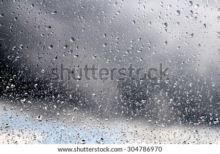 Raindrops on a window pane on the background of a stormy sky. #304786970
