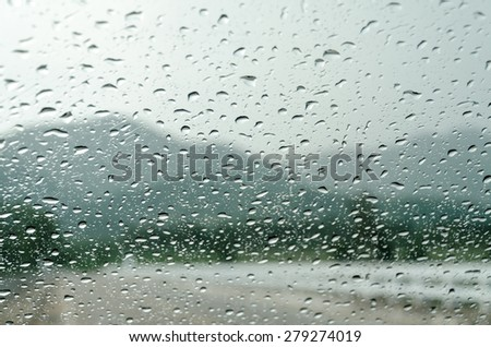 raindrops on auto glass with mountain view