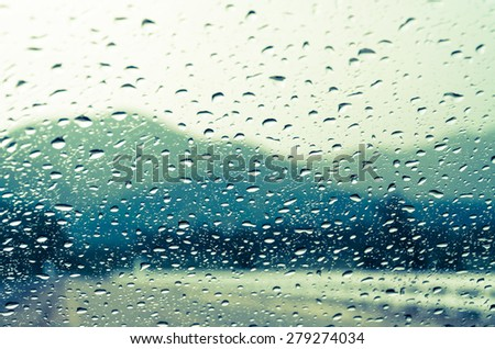 raindrops on auto glass with mountain view in vintage style