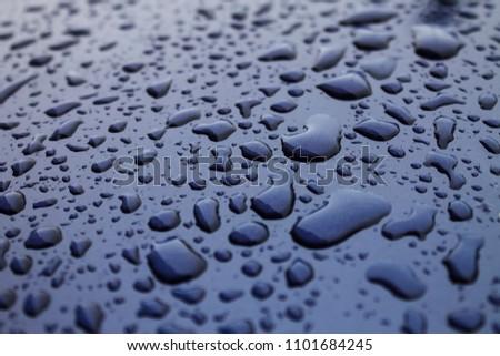 Raindrops on blue bonnet of a car