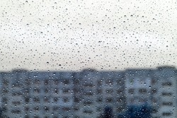 Raindrops on glass, building and gloomy autumn weather outside the window. The concept of longing and loneliness.