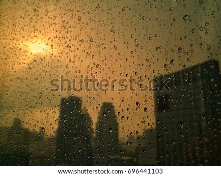 Raindrops on glass window and city background with sunshine in evening #696441103