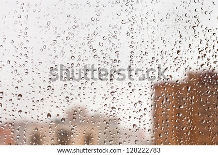 raindrops on glass window with cityscape background