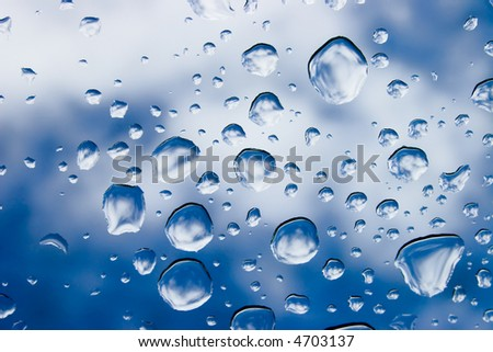 Raindrops on glass with sky on background