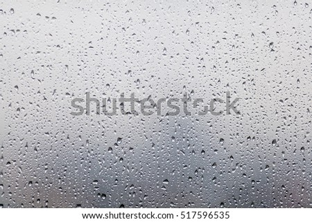 Raindrops on glasses surface. Natural Pattern of rain drops isolated on cloudy background. #517596535