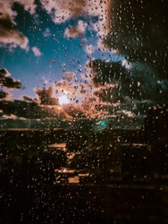 Raindrops on the glass of window against the sky with clouds. The sun after the rain. Amazing view